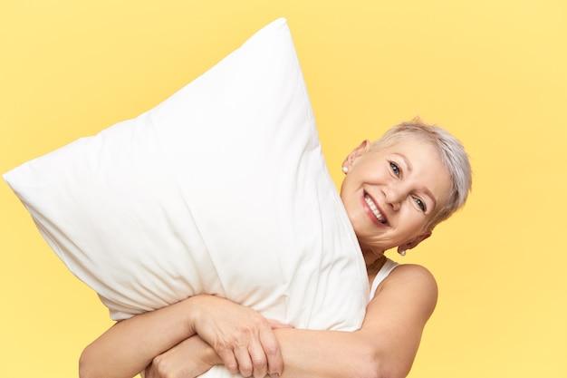 白い羽毛枕を抱きしめ、寝て、長い一日の後に疲れたポジティブな眠そうな成熟したヨーロッパの女性のスタジオショット。