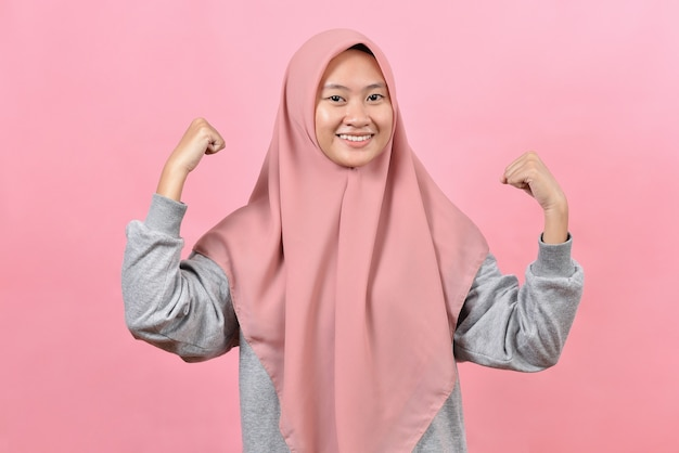 Студийный снимок позитивной молодой азиатской мусульманской женщины, поднимающей руки, показывает, что мышцы притворяются очень сильными, а мощная улыбка нежно носит хиджаб, изолированный на розовом фоне.