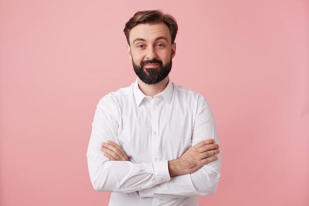 분홍색 벽 위에 포즈를 취하는 동안 공식적인 옷을 입고 가벼운 미소로 정면을 바라 보는 동안 유행 헤어 스타일을 입고 수염을 가진 긍정적 인 젊은 갈색 머리 남자의 스튜디오 샷