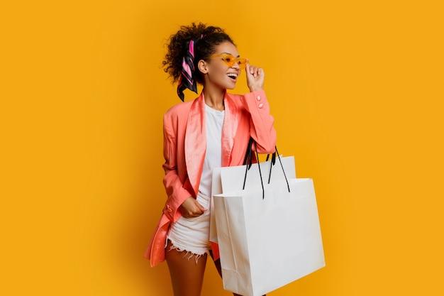 노란색 배경 위에 흰색 쇼핑백 서와 함께 예쁜 흑인 여자의 스튜디오 샷. 유행 봄 유행 모양.