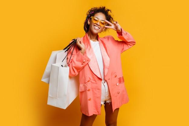 黄色の背景の上に立っている白いショッピングバッグを持つかなり黒人女性のスタジオ撮影。トレンディな春のおしゃれな表情。