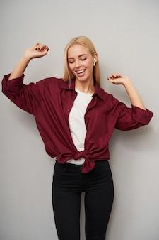 カジュアルな服を着て明るい灰色の背景の上に立って、イヤホンで音楽を聴き、元気に踊っている、体型の良いかなり若い長い髪の金髪の女性のスタジオショット