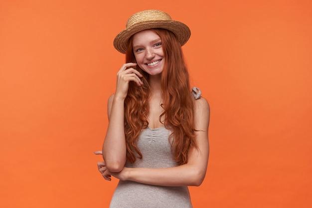 カジュアルな服とカンカン帽の帽子をかぶって、オレンジ色の背景の上に立って、魅力的な笑顔でカメラを見て、彼女のウェーブのかかった髪に触れるかなり若い赤い髪の女性のスタジオショット