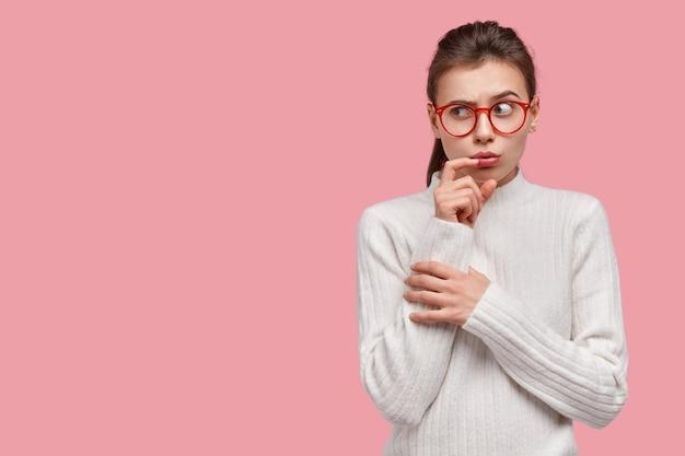 의아해 백인 여자의 스튜디오 샷 입 근처에 손을 유지, 혼란스럽게 옆으로 보이는, 국내 복장, 큰 안경을 입고