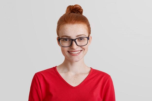 Студийный снимок рыжеволосой молодой улыбающейся девушки носит квадратные очки и красный свитер, будучи в хорошем настроении после продвижения по службе, получает награду за усердную работу и добивается больших успехов.