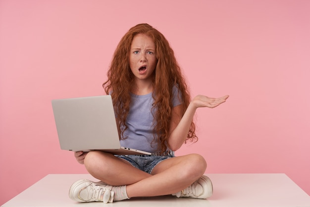 긴 머리를 가진 빨간 머리 곱슬 소녀의 스튜디오 샷 혼란스러운 얼굴로 카메라를보고 다리에 노트북을 들고, 삐와 손바닥을 높이고, 파란색 티셔츠와 청바지 반바지에 분홍색 배경 위에 포즈
