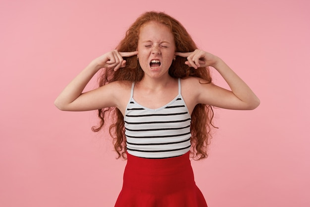 Студийный снимок рыжей длинноволосой кудрявой девушки, стоящей на розовом фоне с закрытыми глазами, вставив указательные пальцы в уши, чтобы избежать громких звуков, в праздничной одежде