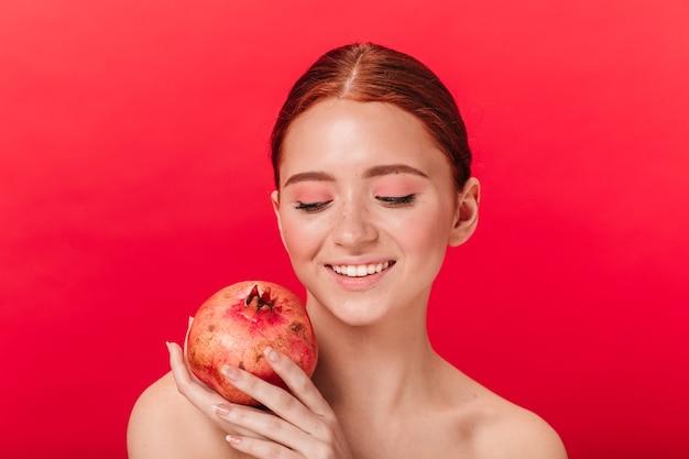 Студия выстрел расслабленной девушки с гранатовым деревом. улыбающаяся женщина имбиря, держащая гранат на красном фоне.