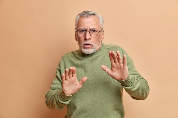 무서워하는 회색 머리 남자의 스튜디오 샷은 방어적인 제스처에 손바닥을 유지하고 공포증이 갈색 벽 위에 고립 된 캐주얼 스웨터와 안경을 착용하는 것을 본다.