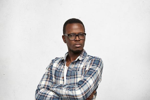 Студийный снимок скептически настроенного подозрительного молодого африканца, стоящего у белой стены