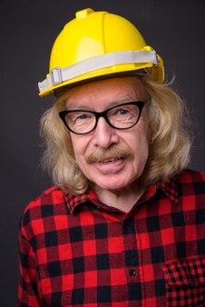 회색 배경 수석 남자 건설 노동자의 스튜디오 샷