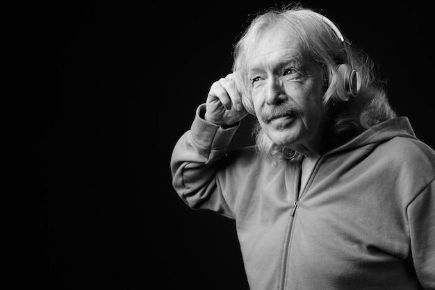 灰色の壁に対して音楽を聴いている口ひげを持つ年配の男性のスタジオショット