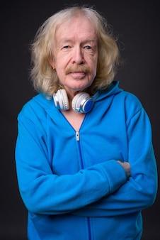 灰色の背景に青いジャケットを着ている口ひげを持つ年配の男性のスタジオショット