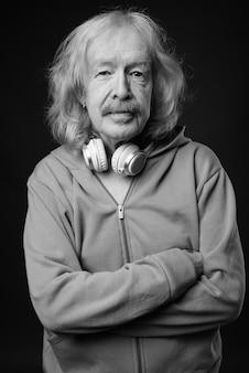 灰色の壁に青いジャケットを着ている口ひげを持つ年配の男性のスタジオショット