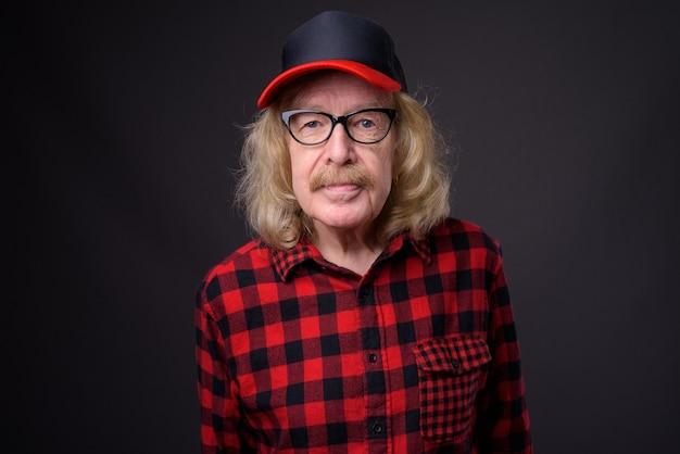 灰色の背景にキャップと眼鏡を身に着けている口ひげを持つ年配の男性のスタジオショット