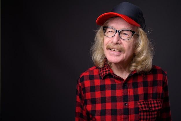 회색 배경에 모자와 안경을 쓰고 콧수염과 수석 남자의 스튜디오 샷