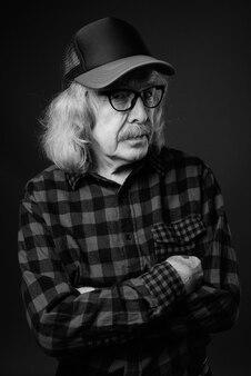 회색 벽에 모자와 안경을 쓰고 콧수염과 수석 남자의 스튜디오 샷