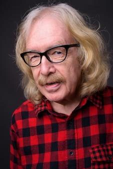 灰色の背景に赤い市松模様のシャツを着て口ひげを持つ年配の男性のスタジオショット
