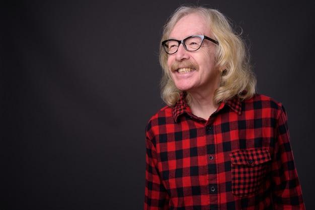 회색 배경에 빨간색 체크 무늬 셔츠를 입고 콧수염과 수석 남자의 스튜디오 샷