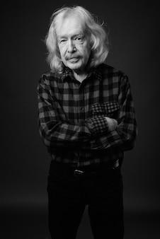 灰色の壁に赤い市松模様のシャツを着ている口ひげを持つ年配の男性のスタジオショット