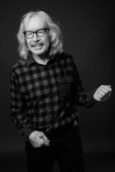 회색 벽에 빨간 체크 무늬 셔츠를 입고 콧수염과 수석 남자의 스튜디오 샷 프리미엄 사진
