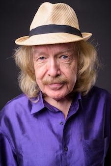 灰色の背景に帽子をかぶって口ひげを持つシニア観光男性のスタジオショット