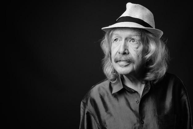 灰色の壁に帽子をかぶった口ひげを持つシニア観光男性のスタジオショット