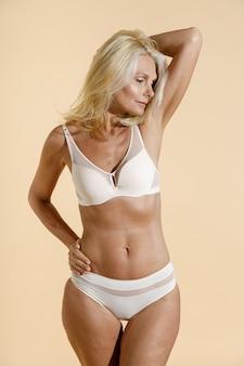 腕を組んで立っている間脇を見てランジェリーで官能的な白人の成熟した女性のスタジオショット