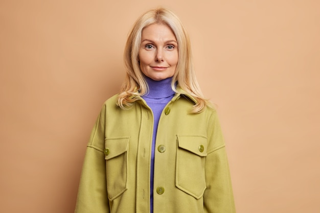 Студийный снимок серьезной женщины среднего возраста со здоровой, ухоженной кожей смотрит прямо в камеру с минимальным макияжем