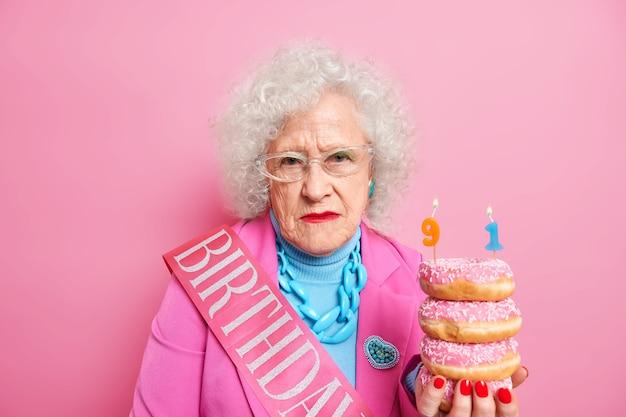 Студийный снимок: серьезная морщинистая женщина с вьющимися седыми волосами выглядит серьезно, держит кучу вкусных глазированных пончиков, одетых в праздничную одежду