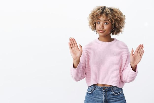 Студийный снимок потрясенной девушки, которая отказывается показывать знак остановки с поднятыми руками