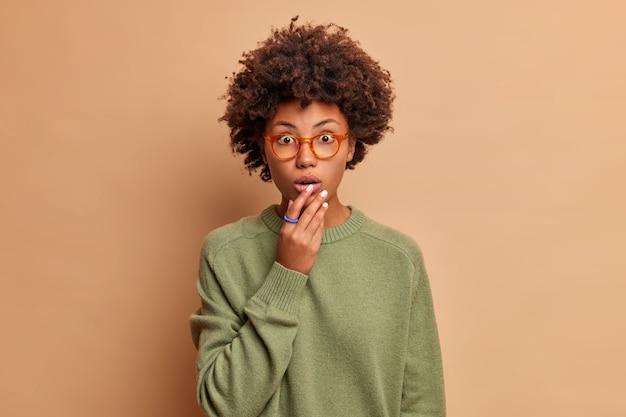 Студийный снимок потрясенной безмолвной кудрявой женщины, которая держит руку у рта, стоит под впечатлением, смотрит в помещении через очки, носит повседневный джемпер, изолированный на бежевой стене, слышит невероятные новости