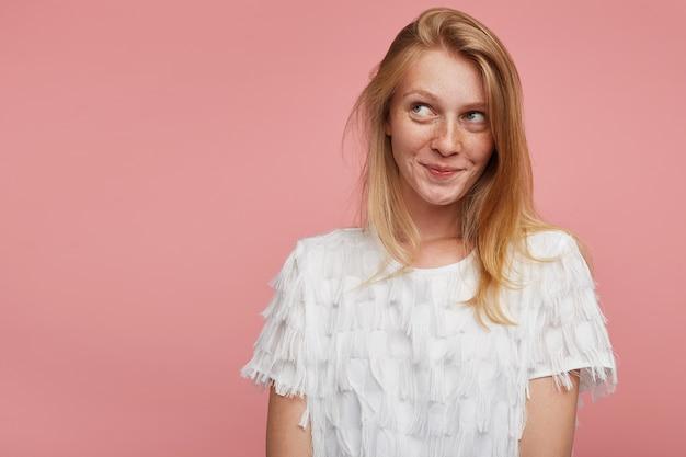 분홍색 배경 위에 포즈를 취하는 동안 흰색 우아한 티셔츠를 입고 긍정적으로 옆으로 보면서 즐겁게 웃고있는 여우 같은 머리를 가진 수줍은 젊은 매력적인 여성의 스튜디오 샷