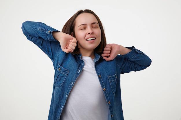 眠そうな若い格好良いブルネットの女性が自分を伸ばして目を閉じたまま手を上げ、白い壁の上でポーズをとるスタジオショット