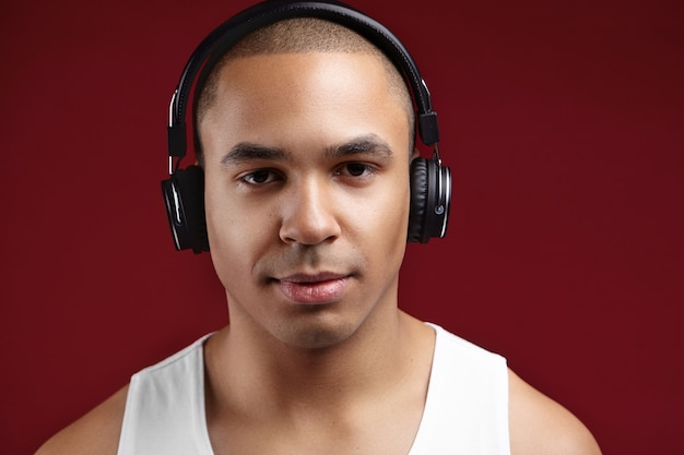 일부 전자 장치에서 온라인 음악 응용 프로그램을 사용하여 세련된 헤드폰을 통해 자신이 좋아하는 아티스트의 새 앨범을 즐기는 자신감이 젊은 아프리카 계 미국인 깨끗한 면도 한 남자의 스튜디오 샷