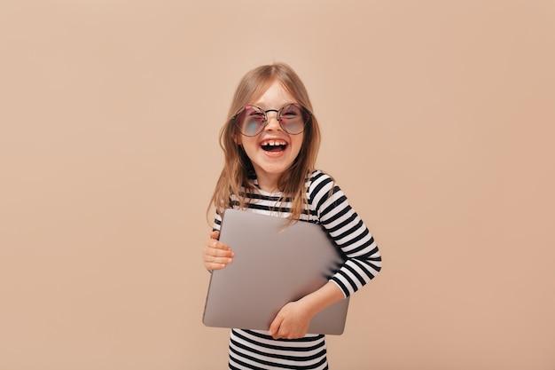 Студийный снимок улыбающейся счастливой милой девушки в модных очках и держащей ноутбук на бежевом фоне