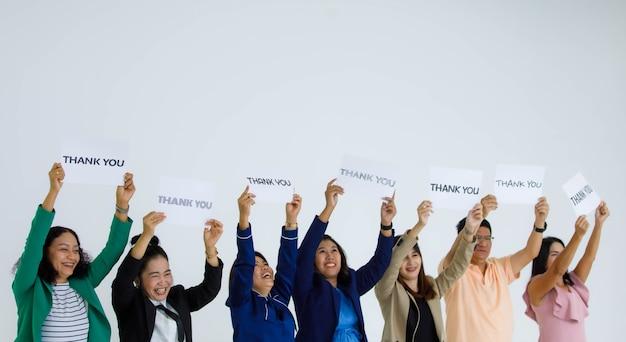웃고 있는 남성 및 여성 장교 직원 그룹이 다양한 글꼴을 들고 있는 스튜디오 샷은 흰색 배경에 있는 고객에게 감사를 표하는 머리 위에 올려진 종이 사인을 감사합니다.