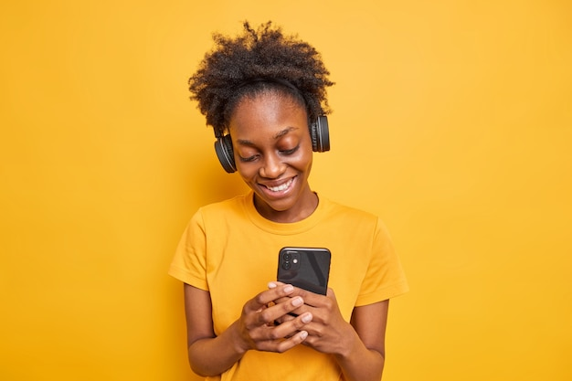검은 피부를 가진 웃고 있는 10대 소녀의 스튜디오 샷은 스마트폰을 통해 문자 메시지를 보냅니다