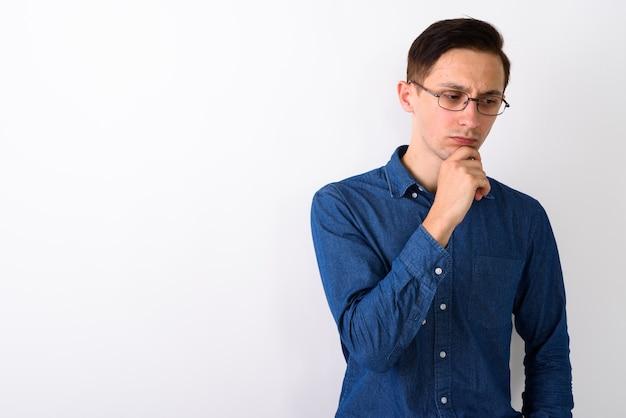 Студийный снимок напряженного молодого человека, думающего и смотрящего вниз, пока