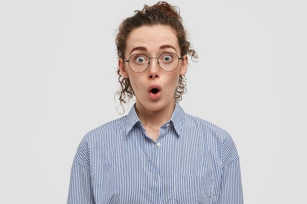 白い壁に向かってポーズをとっている眼鏡をかけた愚かなそばかすのティーンエイジャーのスタジオショット