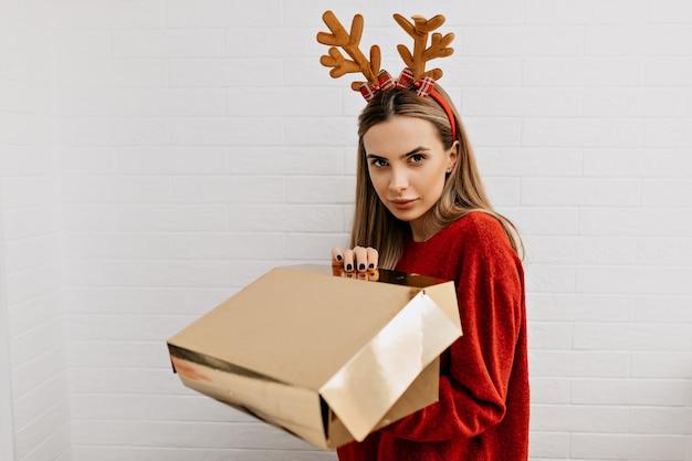 스타일링 유럽 여자의 스튜디오 샷은 카메라를보고 크리스마스 모자에 금 선물을 열고있다