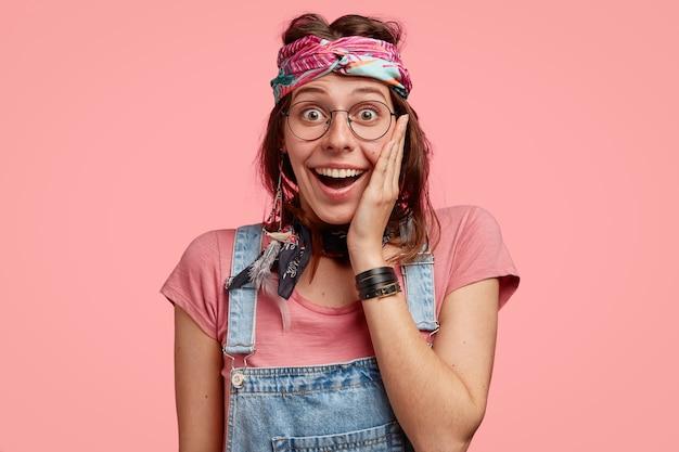 세련된 히피 여성의 스튜디오 샷은 넓은 미소를 지으며 뺨에 손을 대고 눈이 튀었습니다.