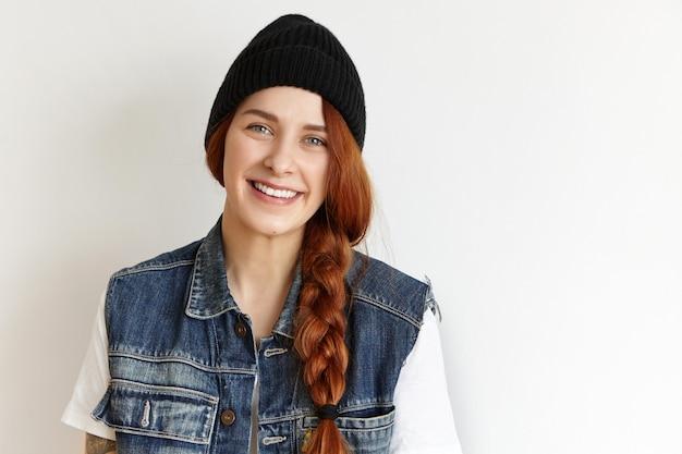 白いtシャツにノースリーブのデニムジャケットを着ているスタイリッシュな若い赤毛の女性のスタジオ撮影