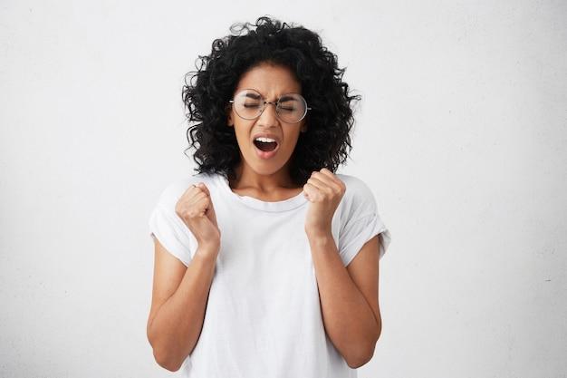 Студийный снимок успешной женщины с африканской прической в повседневной белой футболке
