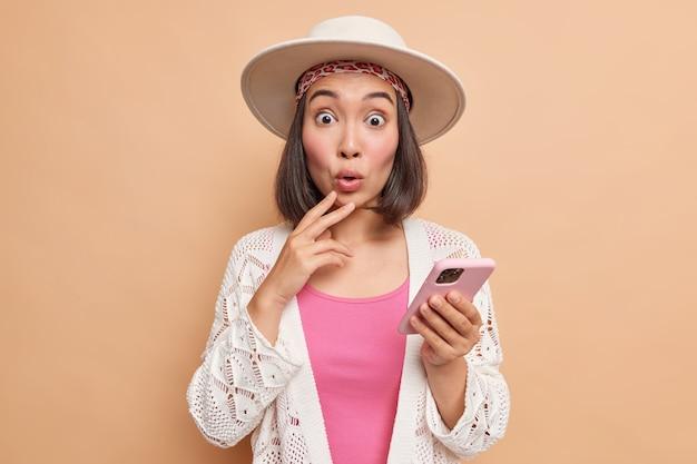 Студийный снимок удивленной азиатской женщины в стильной одежде fedora с очень потрясенным лицом, неожиданным сообщением или комментарием под своим постом в социальных сетях, держит мобильный телефон, использует интернет