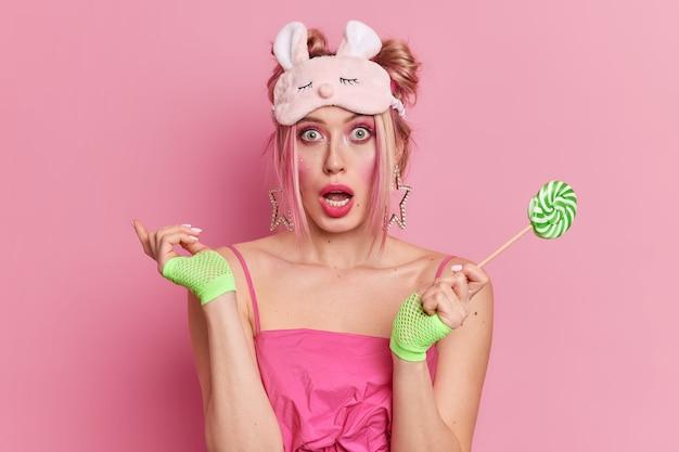 鮮やかなメイクで驚いた金髪の若い女性のスタジオショットは口を開いたままにします