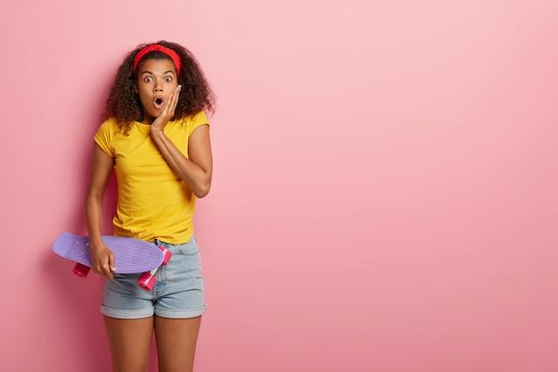 Студийный снимок удивленной темнокожей модели с кудрявой прической