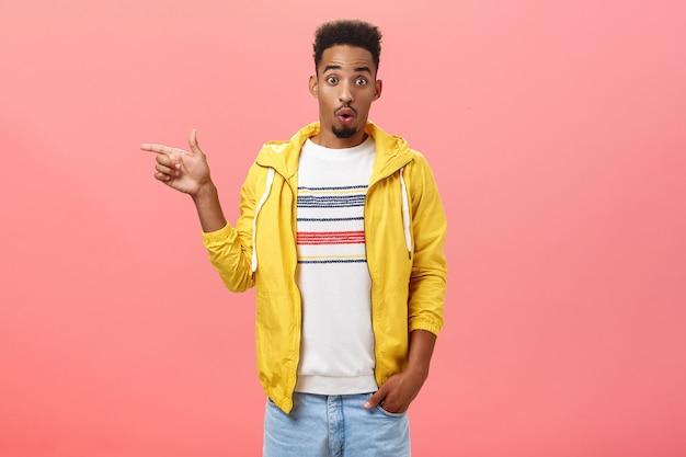세련된 노란색 재킷을 입은 세련된 아프리카계 미국인 남학생의 스튜디오 샷은 분홍색 벽 위에 왼쪽을 가리키는 놀라움에서 눈썹을 올리는 와우 소리로 입술을 접고 있습니다.