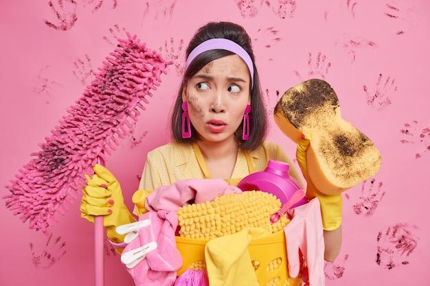 驚いた憤慨した民族主婦のスタジオショットは、家の家具の汚れを取り除き、ピンクの壁に隔離された家事で忙しい汚れたスポンジとモップを保持します