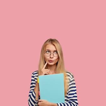 思いやりのある金髪の女性の財布の唇のスタジオショット、深く考え、熟考